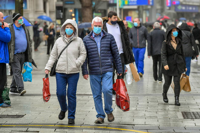 Shoppers carry bags in the centre of Cardiff where shops are open
