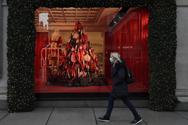 A woman walks past Christmas decorations in a shop window on Oxford Street