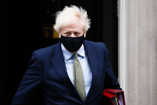 British Prime Minister Boris Johnson leaves 10 Downing Street wearing a face mask