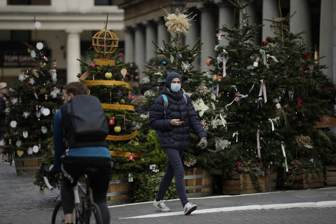 A man wearing a face mask walks past Christmas trees in Covent Garden