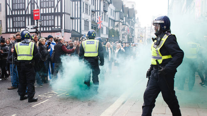 Green smoke rises from a flare thrown as anti-lockdown activists confront police officers