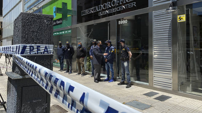 Police guard the entrance to a doctor's practice in Buenos Aires