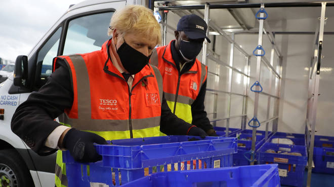 Boris Johnson loads a delivery van with baskets of shopping during a visit to the Tesco Erith distribution Centre in south east London