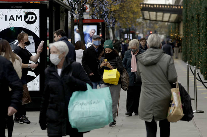 People carry shopping bags as non-essential shops are allowed to reopen