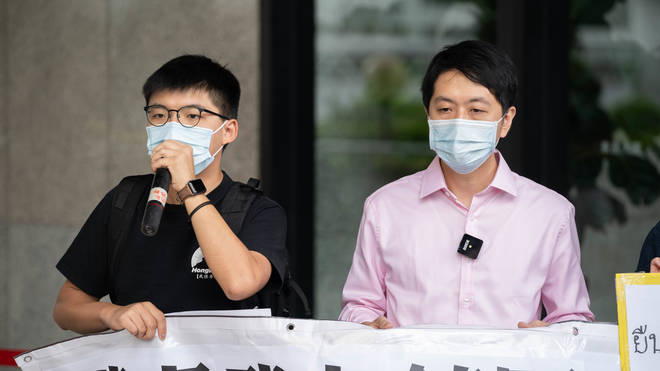 Pro-democracy activist Joshua Wong (left) and lawmaker Ted Hui (right) demonstrate in solidarity with ongoing pro-democracy protests in Thailand