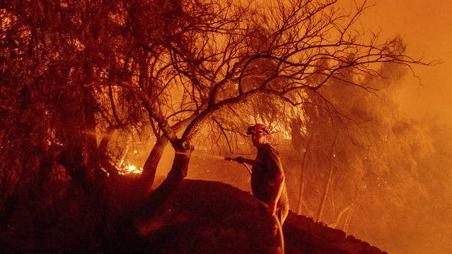 Bruce McDougal hoses down vegetation while working to save his home from the Bond Fire