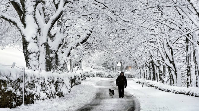 A man walks his dog in snow in Carrshield in the Pennines, near Hexham in Northumberland