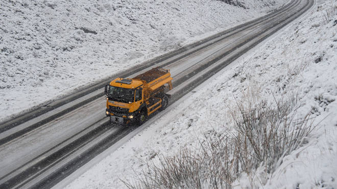 A gritter lorry spreads grit on the A62 as snow falls above the village of Delph, near Manchester