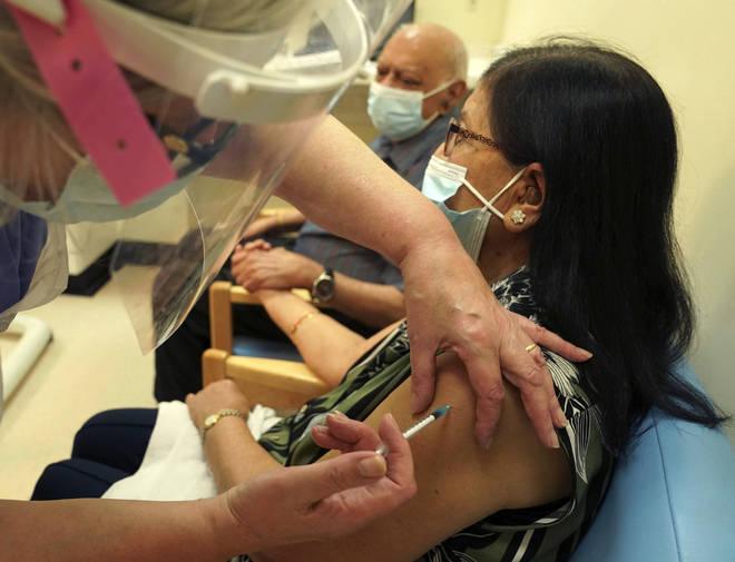 Ranju Shukla, accompanied by her husband Dr Hari Shukla, receives the Pfizer-BioNTech COVID-19 vaccine