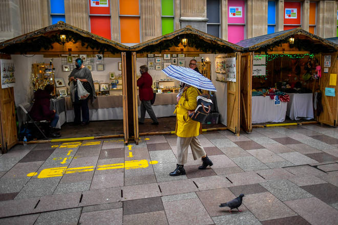 Shoppers walk past Christmas market stalls in the centre of Cardiff