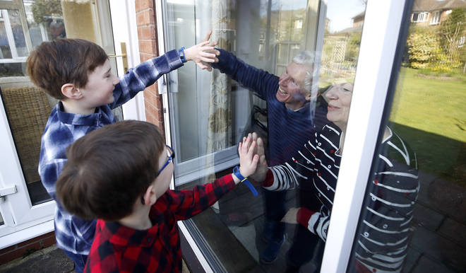 Ben and Isaac talk to their grandparents Sue and Alan through a window, as they self-isolate at their home