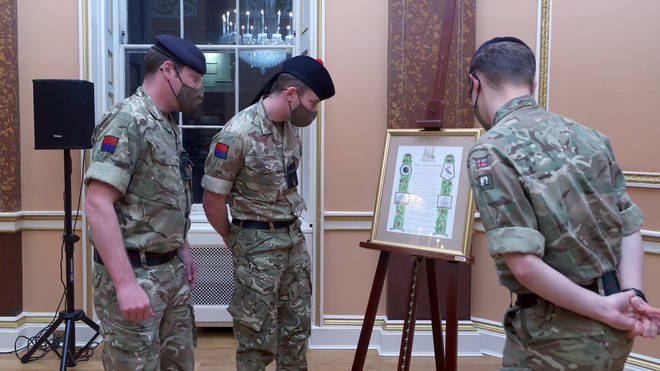 Soldiers look at the scroll that was presented to Brigadier Joe Fossey