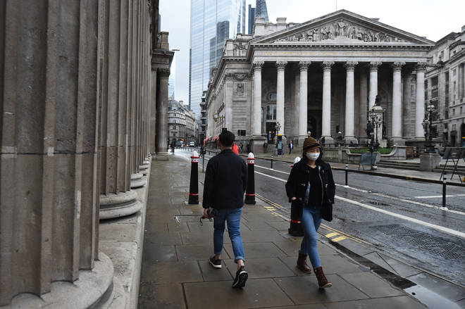 People wearing face masks walk past the Bank of England and the Royal Exchange in London