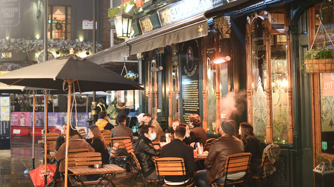 People outside a pub in London's West End as stricter coronavirus measures were announced for the capital