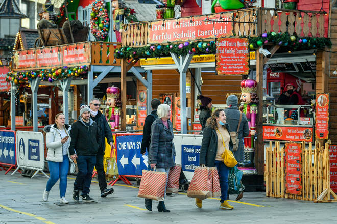 Shoppers pass Christmas market stalls in Cardiff