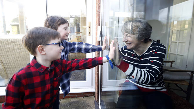 Ben and Isaac talk to their grandmother Sue through a window as she self-isolates at her home
