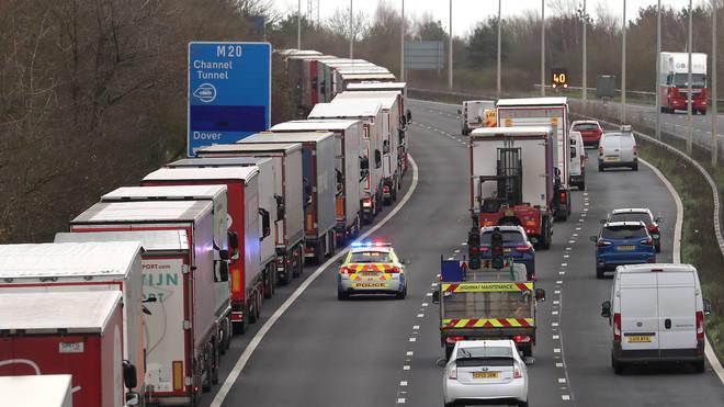 Lorries wait in line along the hard shoulder of the M20 motorway in Kent