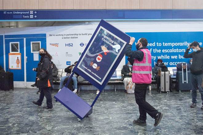 A 'Travelling at Christmas' sign is removed from Euston station, as new laws ban travel from Tier 4 areas such as London.