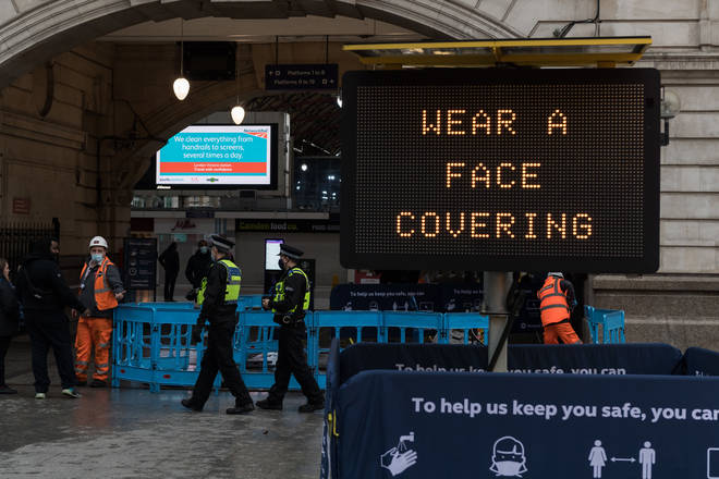 Police officers walk past a 'Wear a face covering' message displayed outside Victoria Station