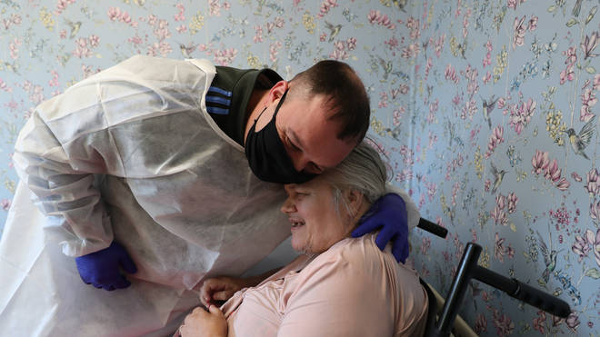 Chris Mills embraces his mother Carol Roberts during a visit at Aspen Hill Village care home