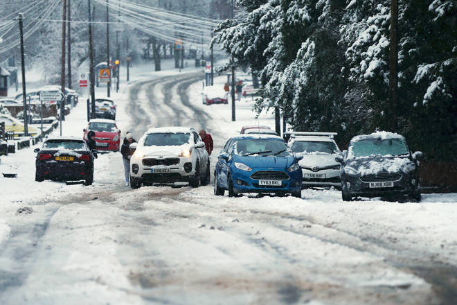 Members of the public help a car that is stuck in the snow as heavy snowfall falls down in Stourbridge, West Midlands