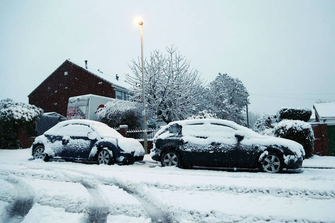 Cars are covered in snow as heavy snow falls down on the West Midlands