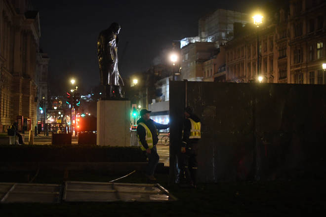 Construction workers put up fencing around the statues in Parliament Square, London, ahead of New Year's Eve
