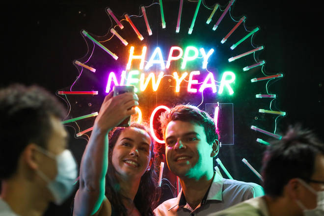 People seen having their photo taken in front of a neon Happy New Year sign as people wearing masks walk past during New Year's Eve celebrations on December 31, 2020 in Melbourne, Australia