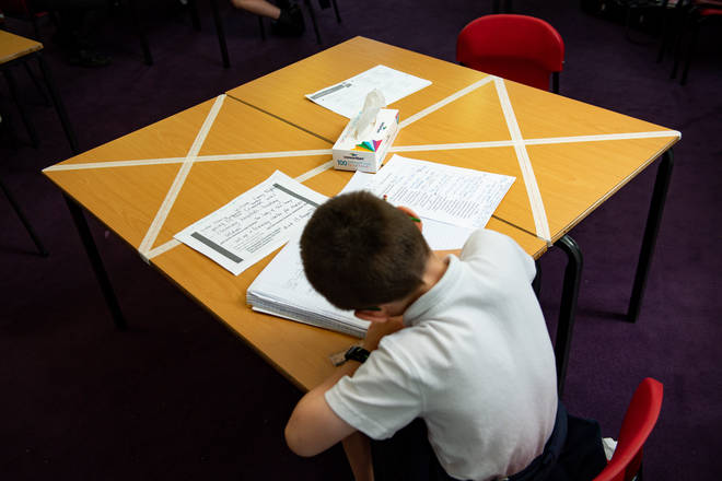 File photo: Social distancing measures as a child studies on a marked table