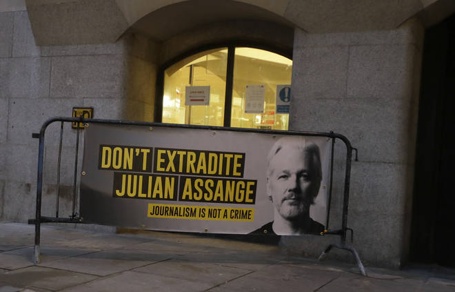 Julian Assange supporters placed a placard on a barrier outside the Old Bailey