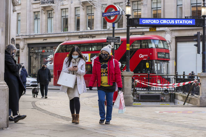 People wearing face masks as a preventive measure against the spread of Covid 19 walk in Oxford Circus
