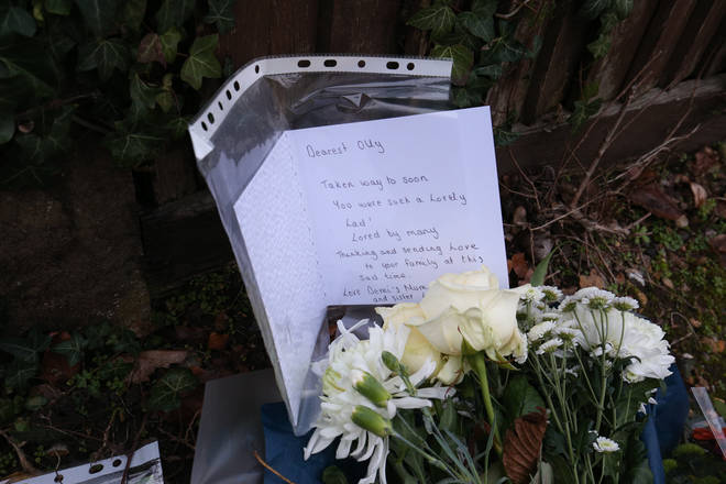 Floral tributes and a card to a boy called Olly left outside Highdown School in Reading