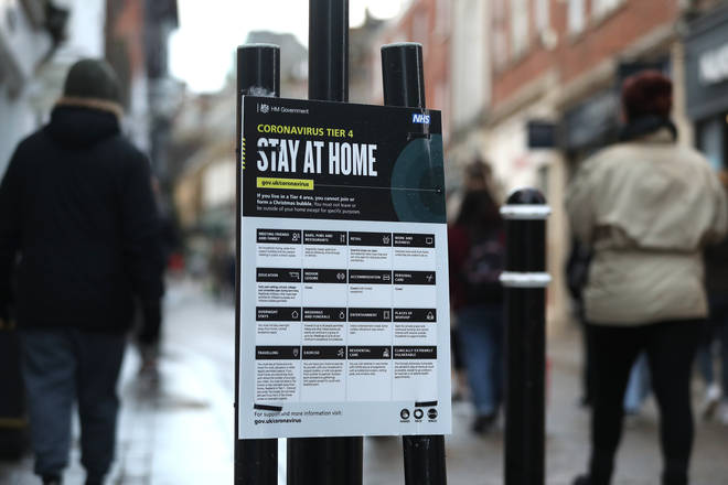 People make their way past a Government coronavirus Tier 4 sign saying 'Stay at Home' on the High street in Winchester