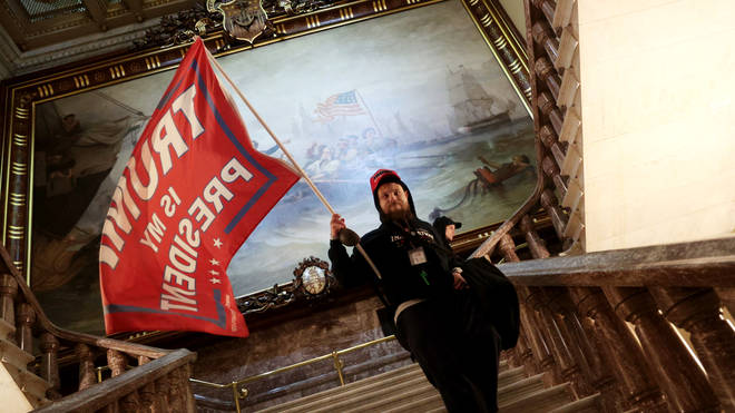 A protester holds a Trump flag inside the US Capitol Building near the Senate Chamber