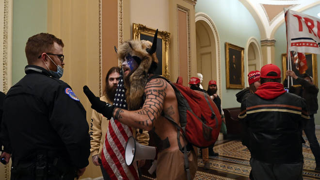 A US Capitol police officer wears agas mask as supporters of US President Donald Trump enter the Capitol