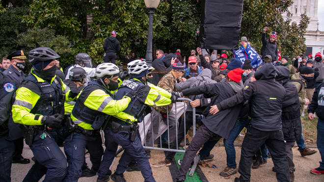 Supporters of President Trump attempt to wrestle a barrier away from Capitol Police in Washington