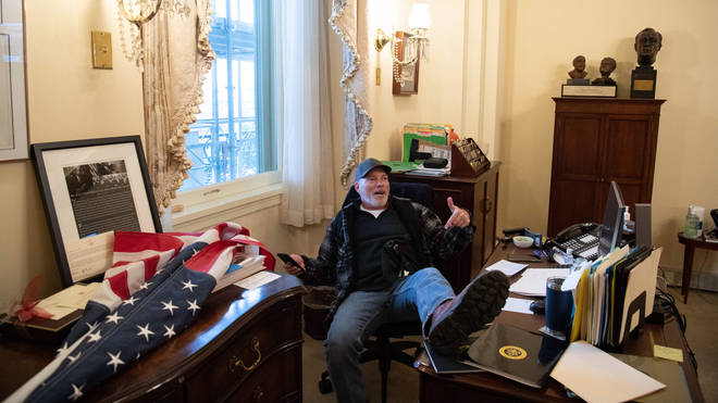 Richard Barnett, a supporter of US President Donald Trump, has been arrested after being pictured with his feet on the desk of Nancy Pelosi