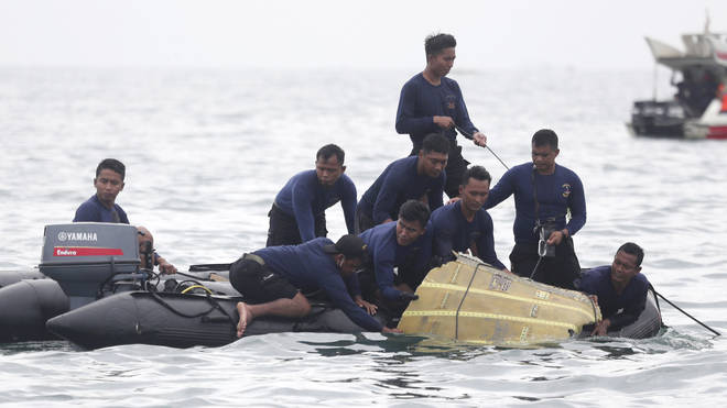 Divers pull wreckage from the passenger plane out of the Java Sea