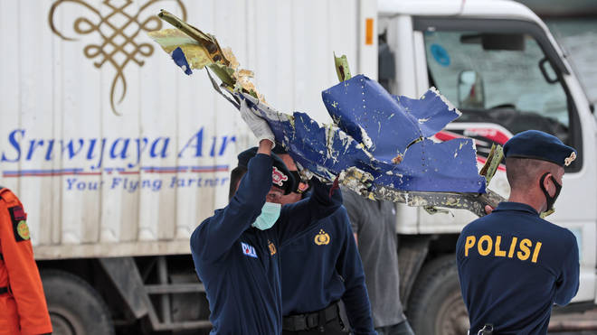 Police officers carry a part of aircraft recovered from the Java Sea where a Sriwijaya Air passenger jet crashed