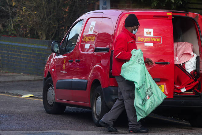 File photo: A postman wearing a face mask holds a postal sack in London