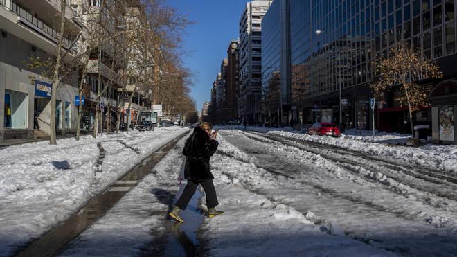 A woman walks through the snow in Madrid, Spain