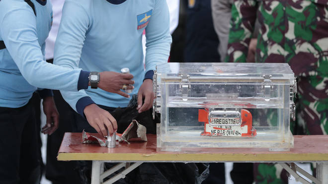Indonesian navy personnel handle a box containing the flight data recorder recovered from the crash site of the Sriwijaya Air flight SJ-182