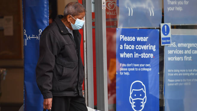 A shopper wearing a face mask leaves Tesco