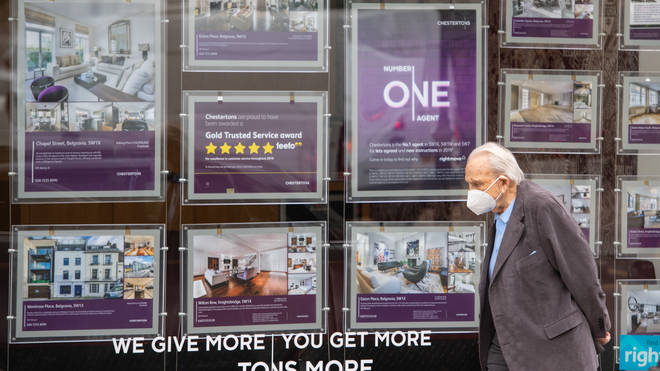 A man wearing a protective face mask passes an estate agents' window in Knightsbridge, London