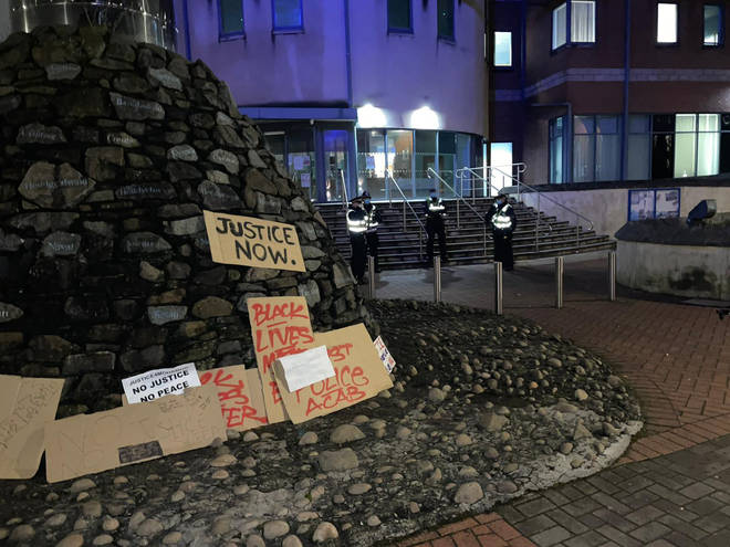Protesters left signs outside the police station following the protest