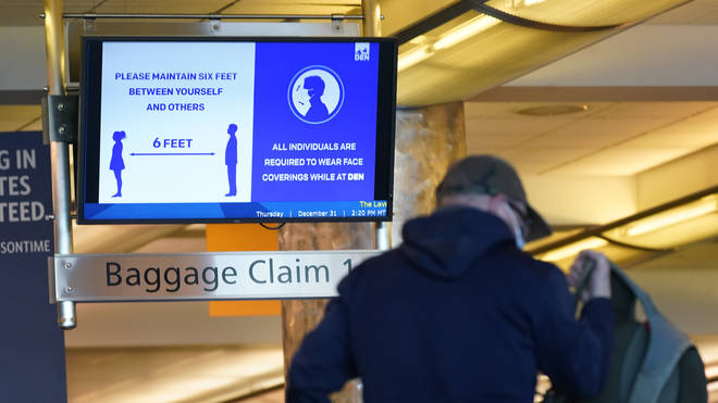 An electronic sign advises travellers to wear face masks and practice social distancing while passing through the main terminal of Denver International Airport