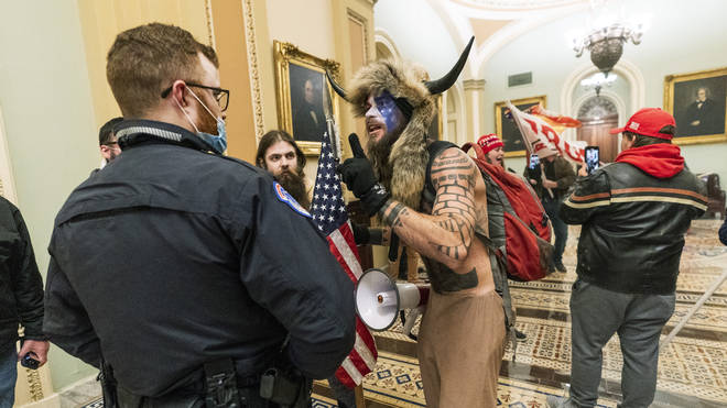 Supporters of President Donald Trump are confronted by US Capitol Police officers outside the Senate Chamber inside the Capitol in Washington