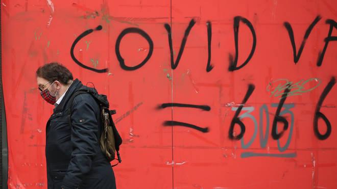 A man walks past coronavirus graffiti in Edinburgh where stricter lockdown measures for mainland Scotland are now in force