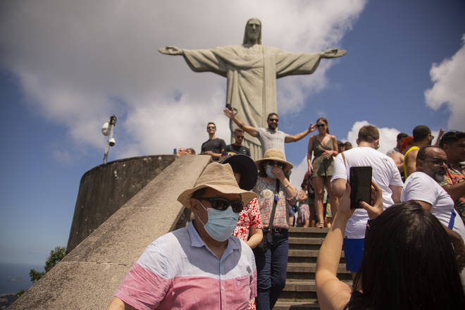 A tourist wears a face mask while visiting Christ the Redeemer