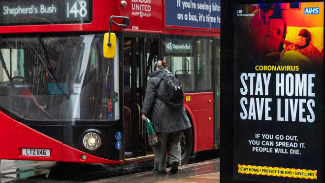 A bus stops by a government coronavirus 'stay home, save lives' advert in central London
